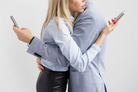 couple on mobiles cuddling looking at phones behind each others back