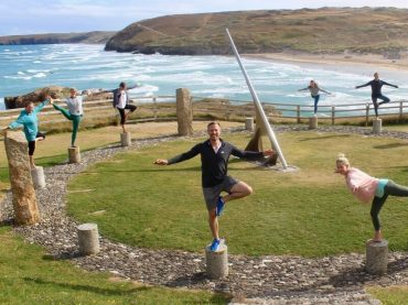 people standing on stones doing yoga pose on cliff next to sea easter yoga retreat cornwall