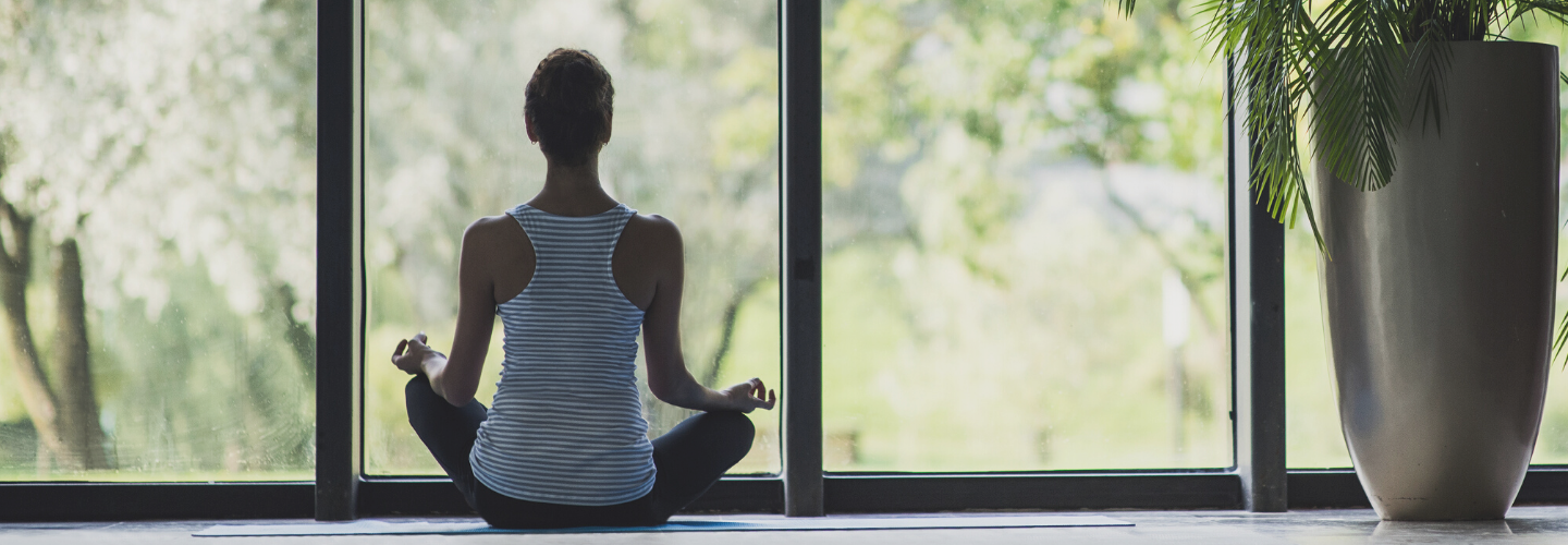 woman sat meditation pose looking out window